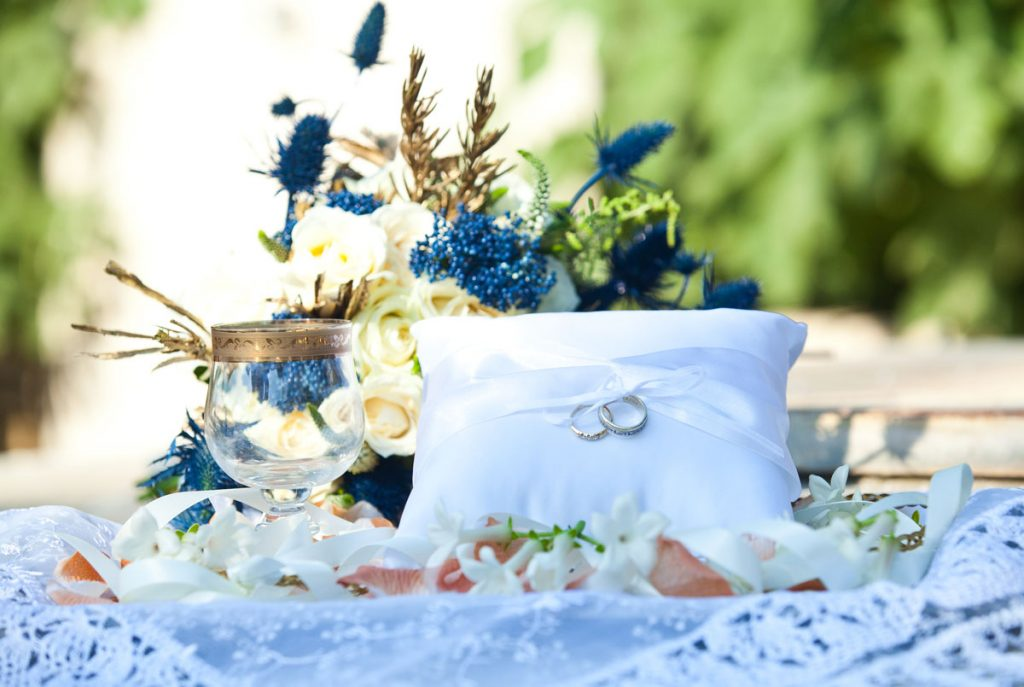 The tray with stefana, koufetes, rings, rice, a cup and rose petals